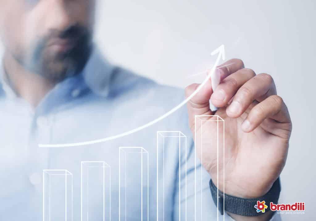 Homem desenhando um gráfico representando a crescente em vendas